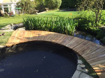 The finished garden pond and wooden bridge walkway